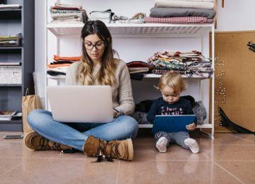 Selbstorganisation im Homeoffice: Mutter und Tochter sitzen vor Kleiderschrnk und arbeiten auf Device.