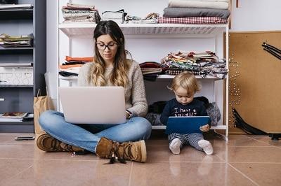 Zur Ergänzung des Textes. Mutter und Tochter sitzen vor Kleiderschrnk und arbeiten auf Device.
