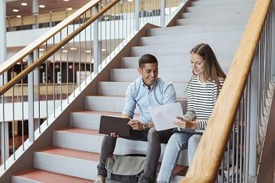 Zur Ergänzung des Textes. Studenten sitzen auf Treppe und tauschen sich über Dokument aus.