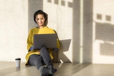 Junge Frau sitzt auf dem Boden und arbeitet am Laptop