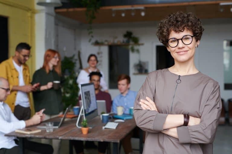 Weibliche Führungskraft mit Brille vor einem sechsköpfigen Team stehend