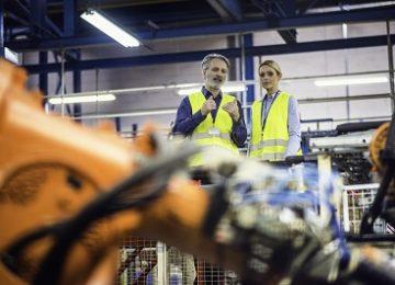 Change Management Seminar: Älterer Kollege und jüngere Kollegin in Fabrik im Gespräch